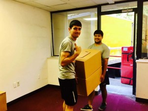 Two Hoboken movers holding a large box, smiling