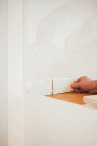 Man placing tiles - renovate a bathroom