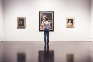 A woman standing in front of three paintings in an art gallery