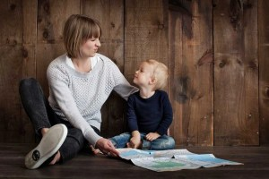 A woman talking to her son while sitting on the floor and holding a map - prepare your child for a move by explaining everything to him.