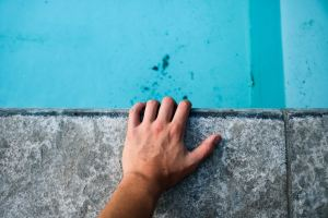 Image of a hand holding a concrete block