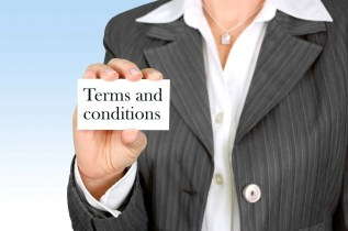 """A woman holding a small card with the words """"Terms and conditions"""" on it"""