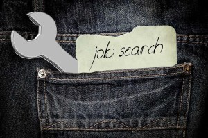 "Denim pants with a wrench and a piece of paper with the words ""job search"""
