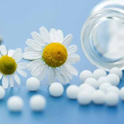 01 - chamomile-flower-and-homeopathic-medication-on-blue-surface.jpg