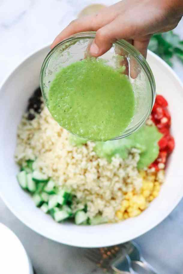 Hand pouring green cilantro dressing over quinoa salad ingredients.