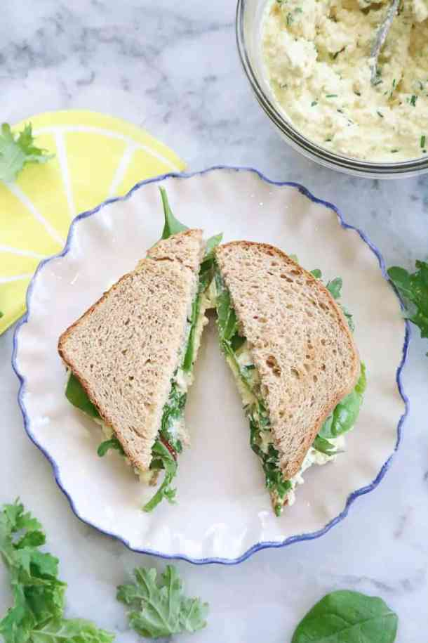 Over head view of Vegan Egg Salad sandwich cut on a plate.