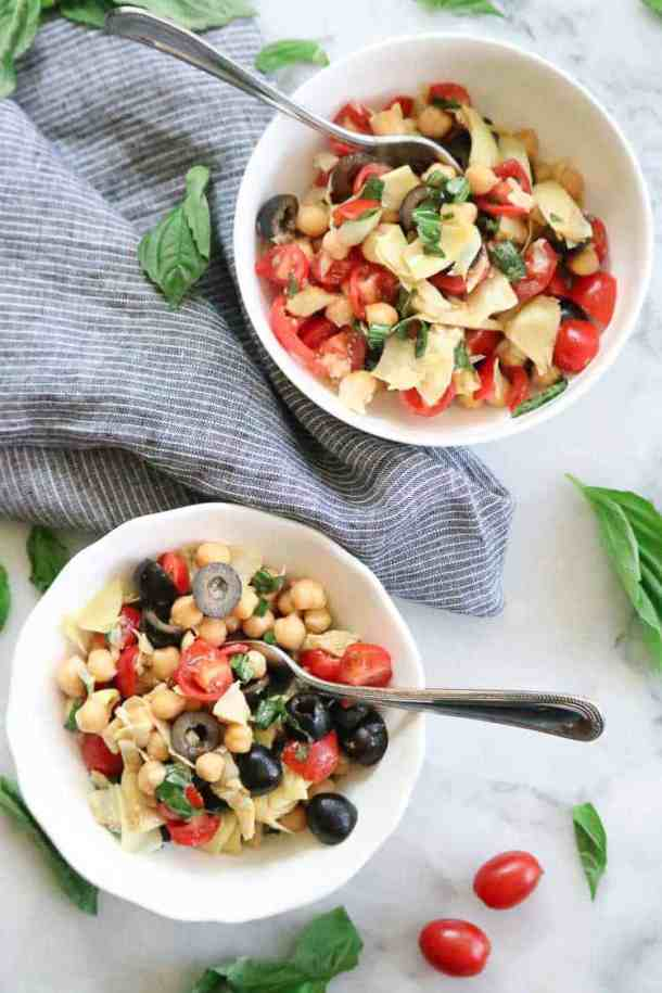 two bowls of artichoke salad with grape tomatoes, and basil leaves as a garnish