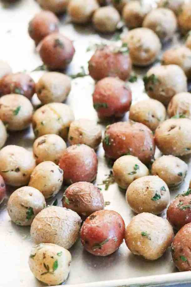 Red and white roasted baby potatoes on a silver baking tray.