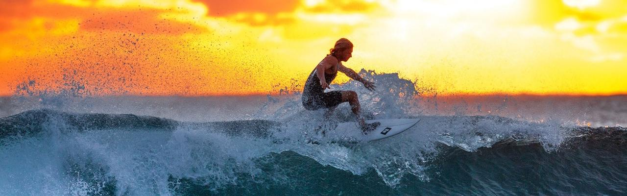a surfer surfing during sunset