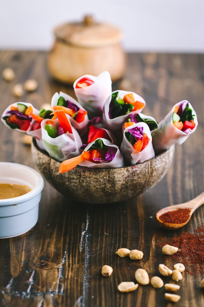 Picture of vegan spring rolls in coconut bowl on wooden table