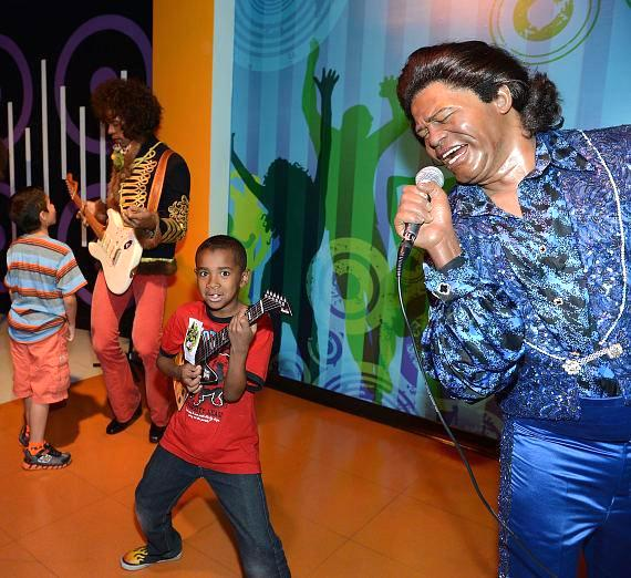 Children pose with wax figure of James Brown at Madame Tussauds Las Vegas