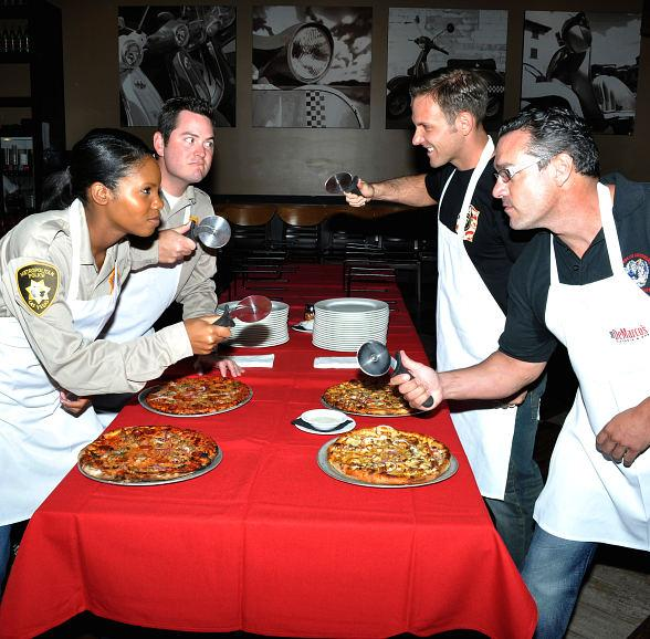Members of the Friends of Las Vegas Metro Police Foundation and Firefighters of Southern Nevada Burn Foundation engage in friendly competition at Dom DeMarco's Pizzeria.