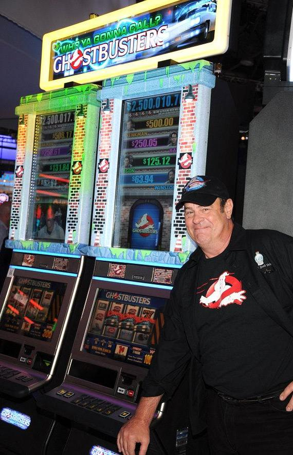 "Actor Dan Aykroyd poses with ""Ghostbusters"" slot machine"