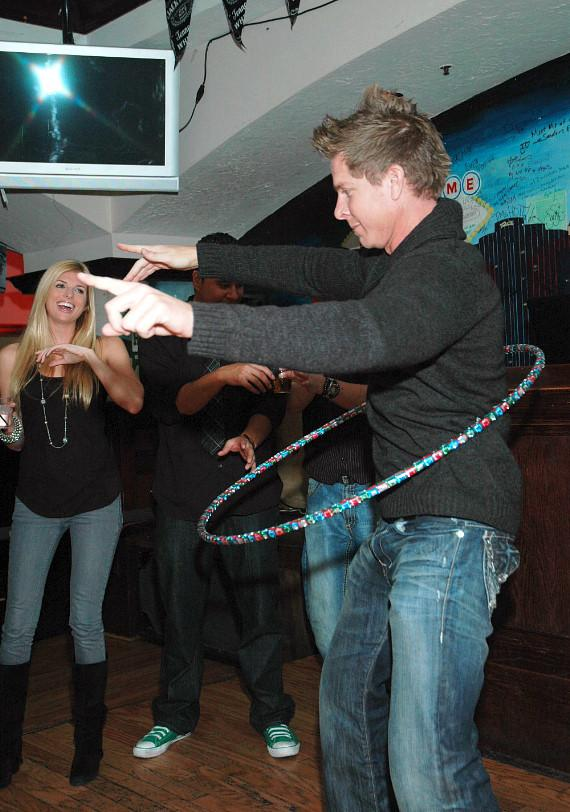 Mark Long playing hula-hoop with Trishelle Cannatella encouraging him with laughter at McFadden's Restaurant and Saloon