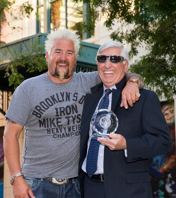 """Guy Fieri posing with President of Hospitality Bob Morse and his Best of Las Vegas """"Best Gastropub"""" award"""