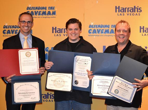 "Celebrating the sixth anniversary of ""Defending the Caveman"" in Las Vegas, Christian Stuart, Harrah's regional vice president and assistant general manager presents the new leading caveman, Chris Allen, and local producer, John Bentham, with several certificates of recognition from local government officials"