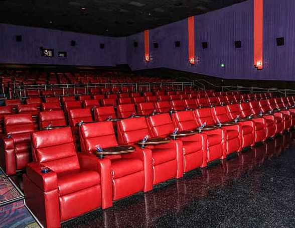 Luxury+ Cushioned leatherette reclining seats with powered footrests and attached snack tables