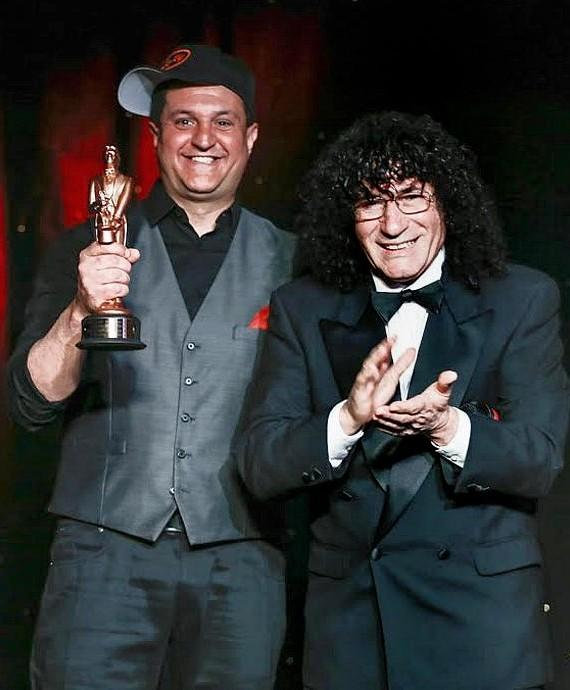 Douglas 'Lefty' Leferovich receives award from Tony Hassini, President of the International Magicians Society