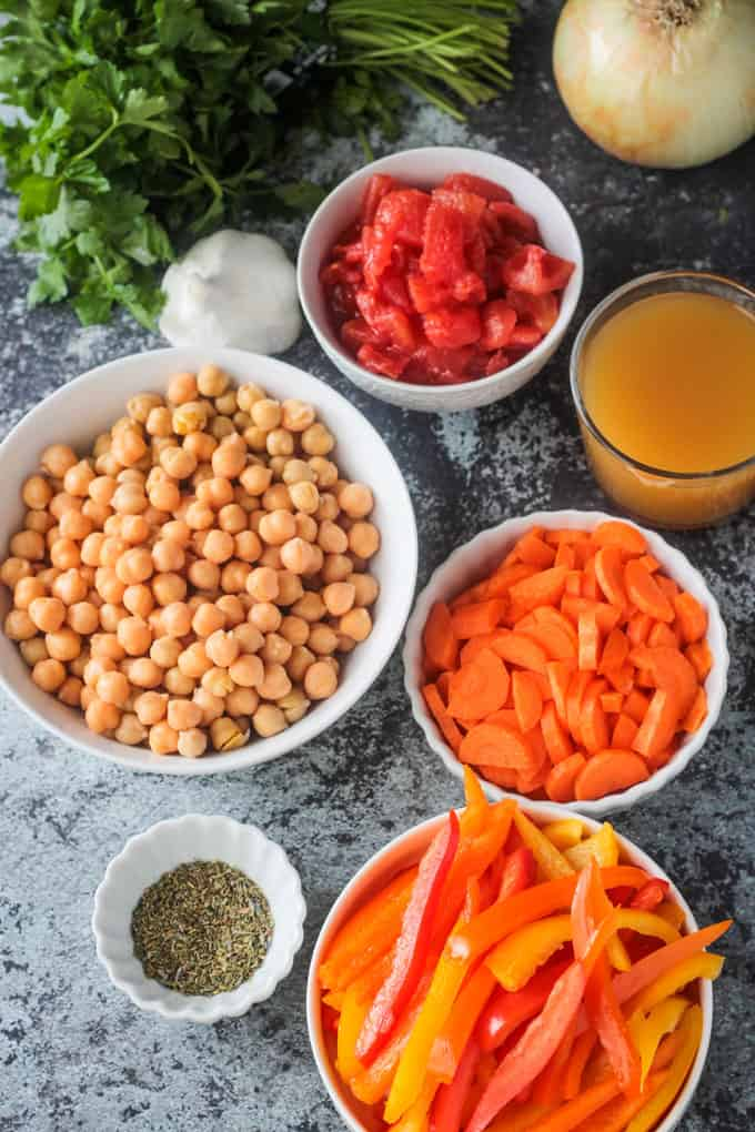 Individual bowls of ingredients: chickpeas, tomatoes, broth, carrots, peppers, herbs, onion, and garlic