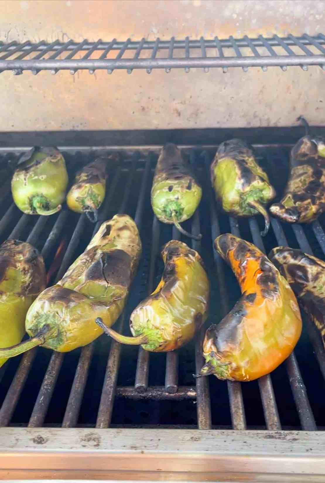 Red and green peppers being roasted on an outside grill