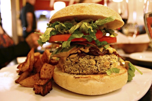 Green Lentil And Green Chili Burger Corn meal crusted vegetable burger made with green lentils, green chilies, red onion, cilantro, quinoa and roasted corn. Topped with chipotle aioli, shredded romaine, green chili cashew 'cheese' and crisp tortilla strips. Served on a toasted Kaiser roll with rosemary-roasted potatoes. This was my favorite! I want one of these right now, actually – so delicious!