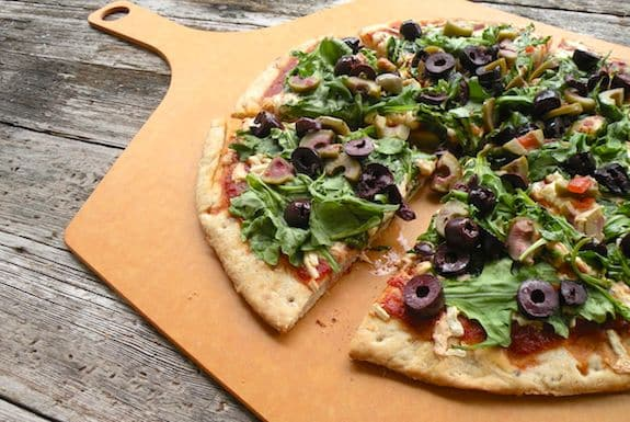 Spinach or arugula and olive pizza