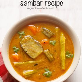 sambar served in a cream bowl on a white board with a red & white checkered napkin on the side