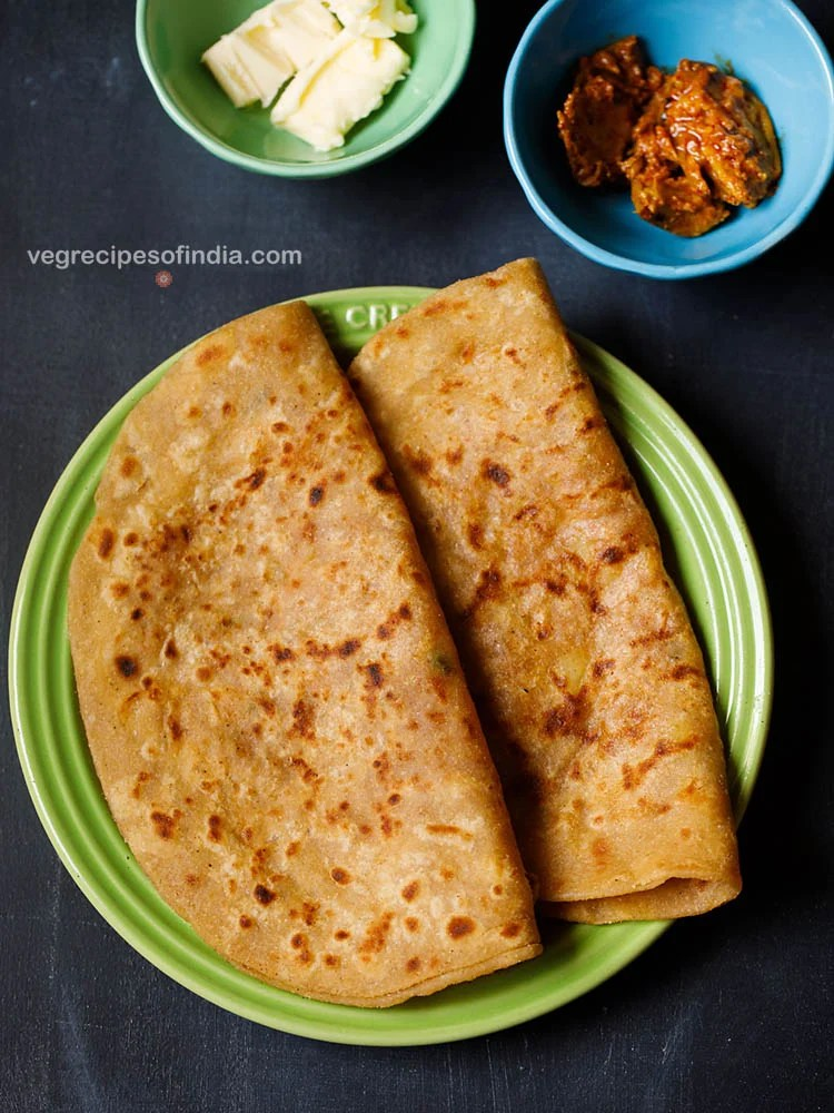 aloo paratha folded and placed on a green ceramic plate on a dark bluish board. sides of butter cubes and mango pickle served in two small ceramic bowls.