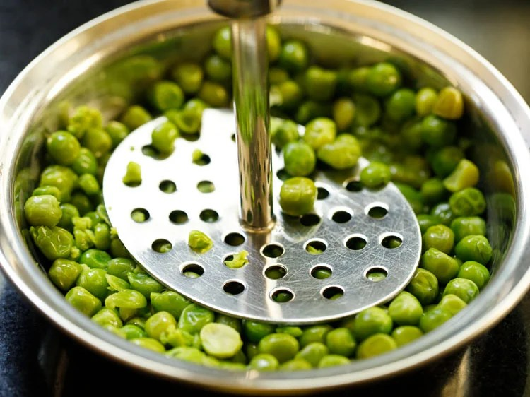 drained steamed peas being mashed in a bowl