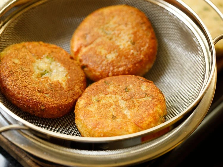 fried aloo tikki placed in a strainer kept on top of a bowl
