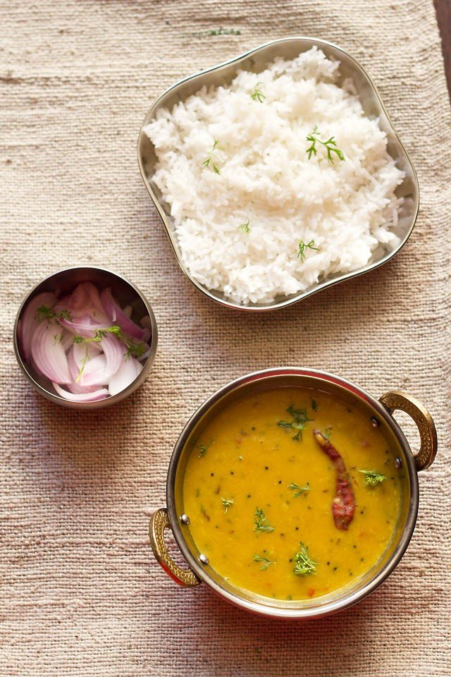 dal fry in a small wok (Indian kadai) with a bowl of sliced red onions and a square plate of steamed rice on a cream jute table cloth