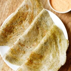 three pesarattu or moong dal dosa folded and kept on a white plate with a orange colored coconut chutney in a side bowl