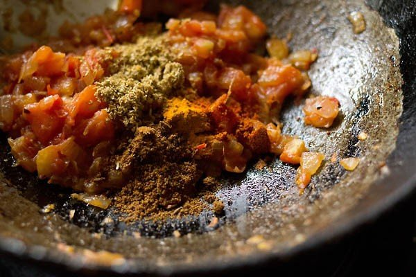 spice powders added to masala mixture in the pan