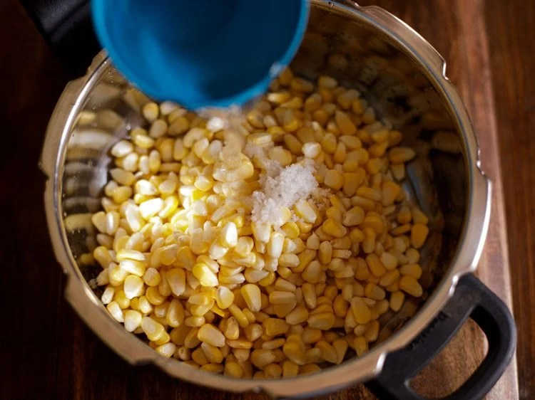 Add the rinsed corn kernels in a pressure cooker with salt and water