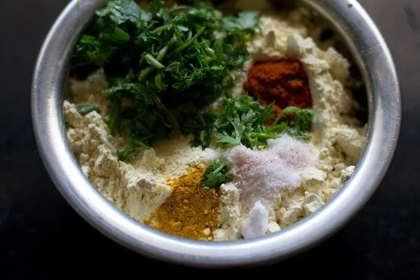 in a mixing bowl add gram flour coriander leaves and spices