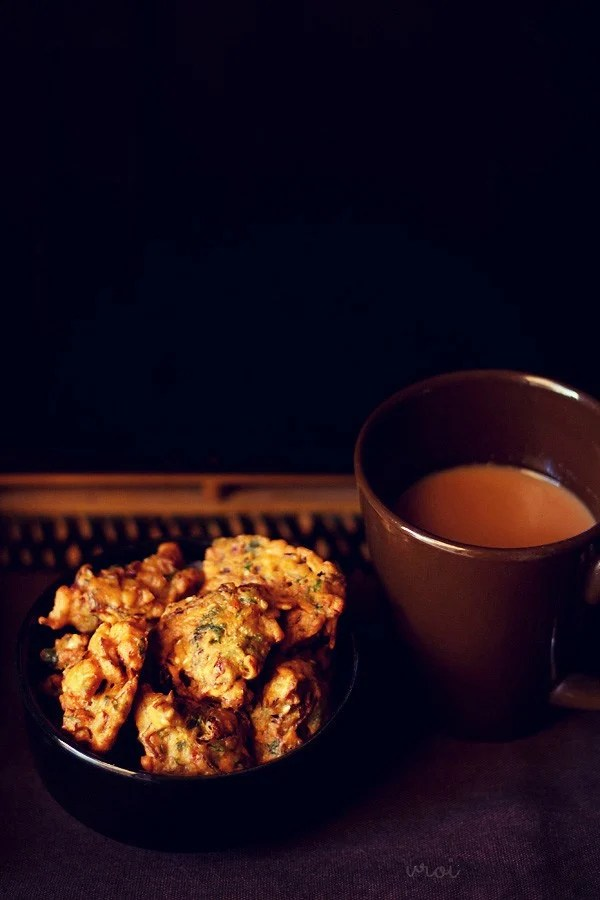 cabbage pakoda served on a black bowl with tea