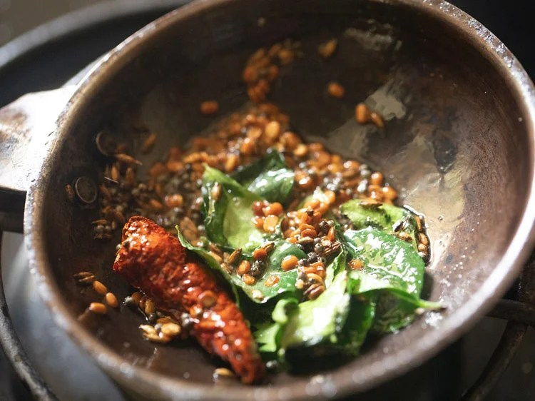 showing the crisped curry leaves and fried red chili in the tadka pan for making tamil nadu style coconut chutney recipe