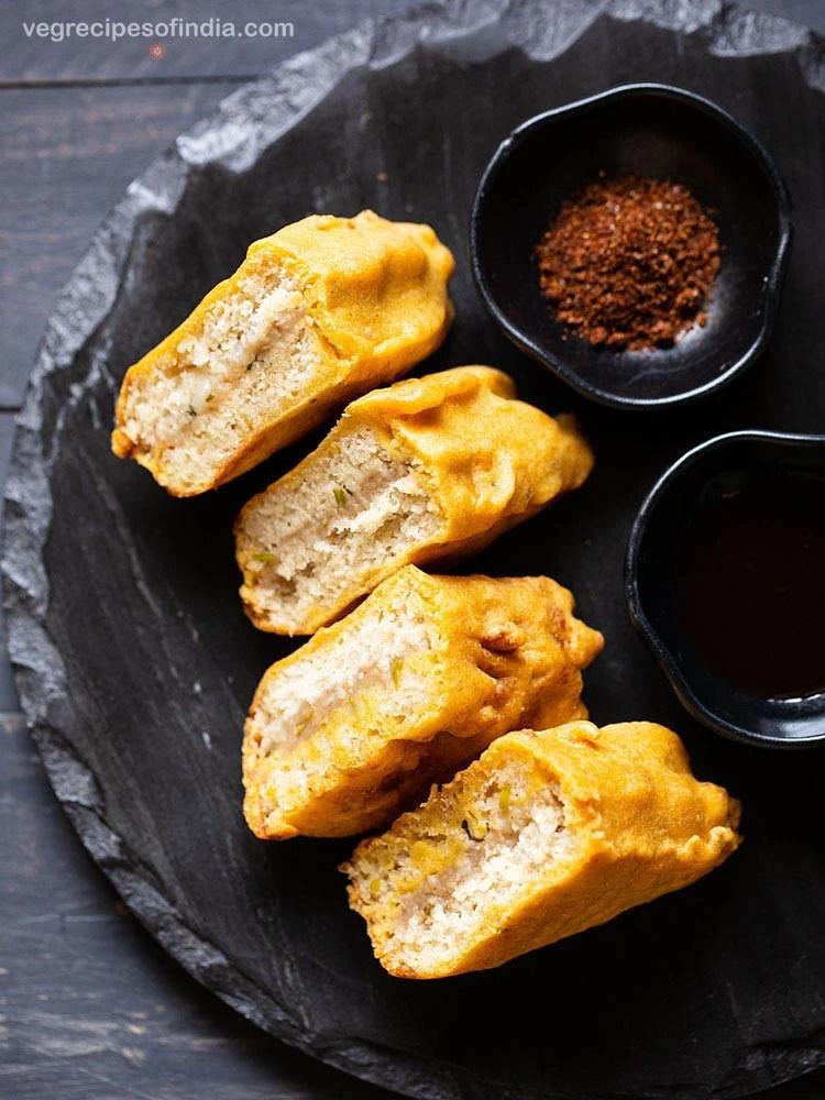 stuffed bread pakoda slices on a black slate board with two black small bowl of dry garlic chutney and tamarind chutney
