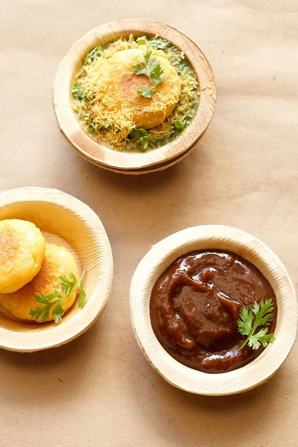 sweet tamarind chutney garnished with a coriander sprig and served in an Areca leaf bowl on a light brown paper with potato patties in areca leaf bowls on left side and ragda patties chaat on top