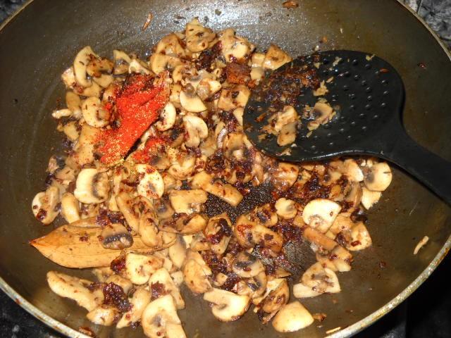 adding chili powder to mushroom biryani mixture