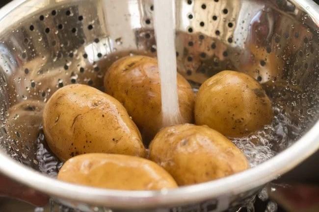 potatoes being rinsed in fresh water in a colander