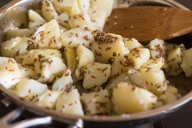 mixing potatoes with cumin and green chillies