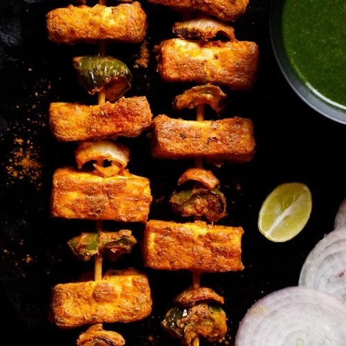 two grilled paneer tikka skewers kept on a black slate board with a bowl of cilantro dip on top right, one lemon wedge below the bowl and a few onion rounds near the lemon wedge