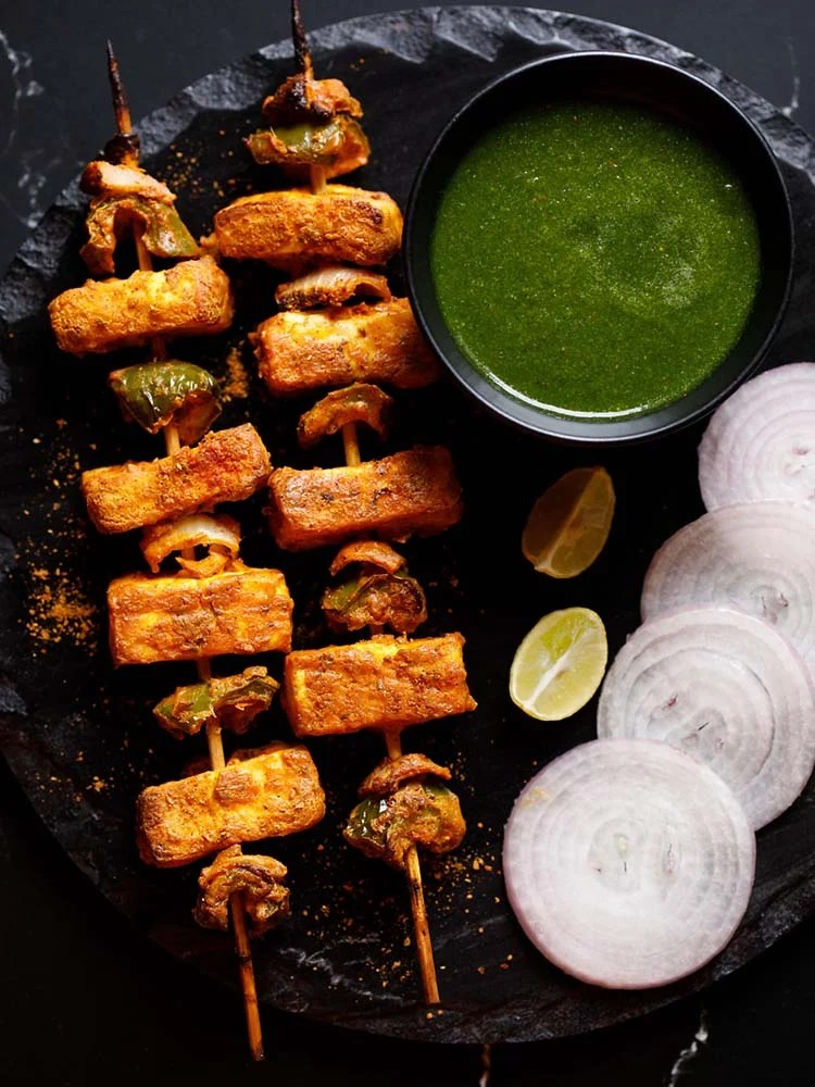 two grilled paneer tikka skewers kept on a black slate board with a bowl of cilantro dip on top right, two lemon wedges below the bowl and some slices onion rounds near the lemon wedges