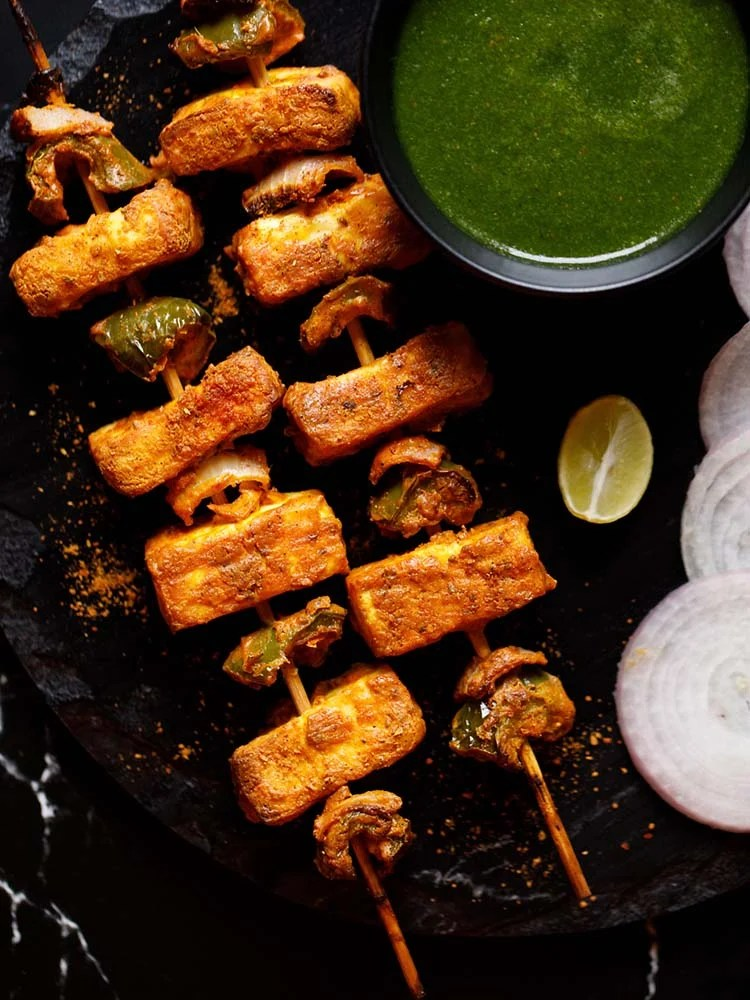 wo grilled paneer tikka skewers kept on a black slate board with a bowl of cilantro dip on top right, one lemon wedge below the bowl and a few onion rounds near the lemon wedge