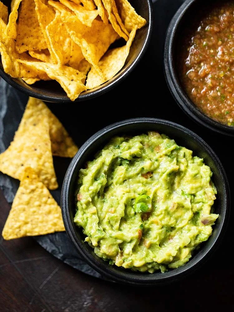 avocado served in a black wooden bowl with a side black bowl of nachos and tomato salsa