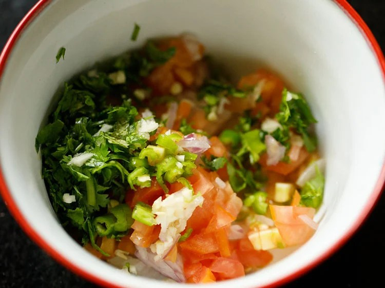 chopped onions, tomatoes, peppers, coriander leaves, garlic in a mixing bowl