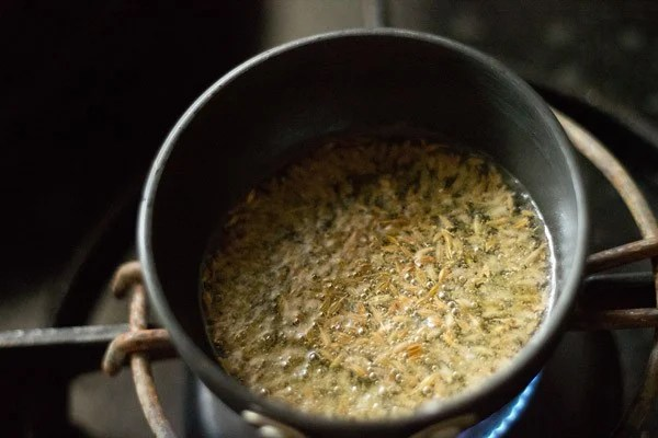 cumin seeds being fried in oil in a small round pan