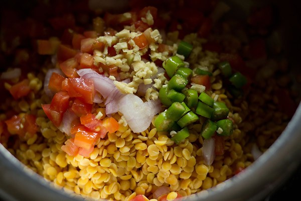 chopped onions, ginger, tomatoes and green chillies added to the lentils in the pressure cooker