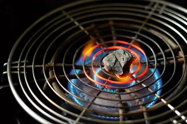a small piece of charcoal kept on a wired pan and being burnt on a gas-stove flame
